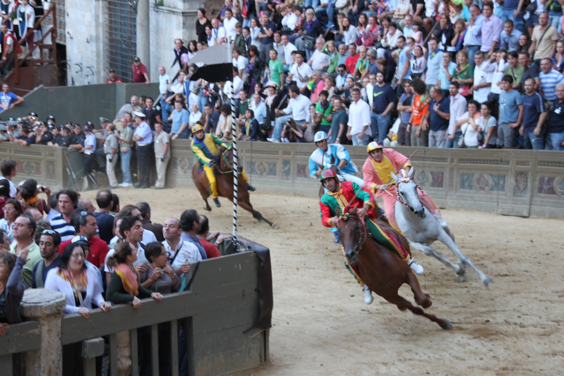 Photo of race horses racing in the Palio of Siena in the Piazza del Campo