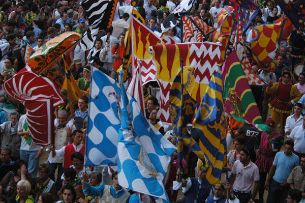 Photo of technicolour contrada district flags in Siena at the Palio horse race