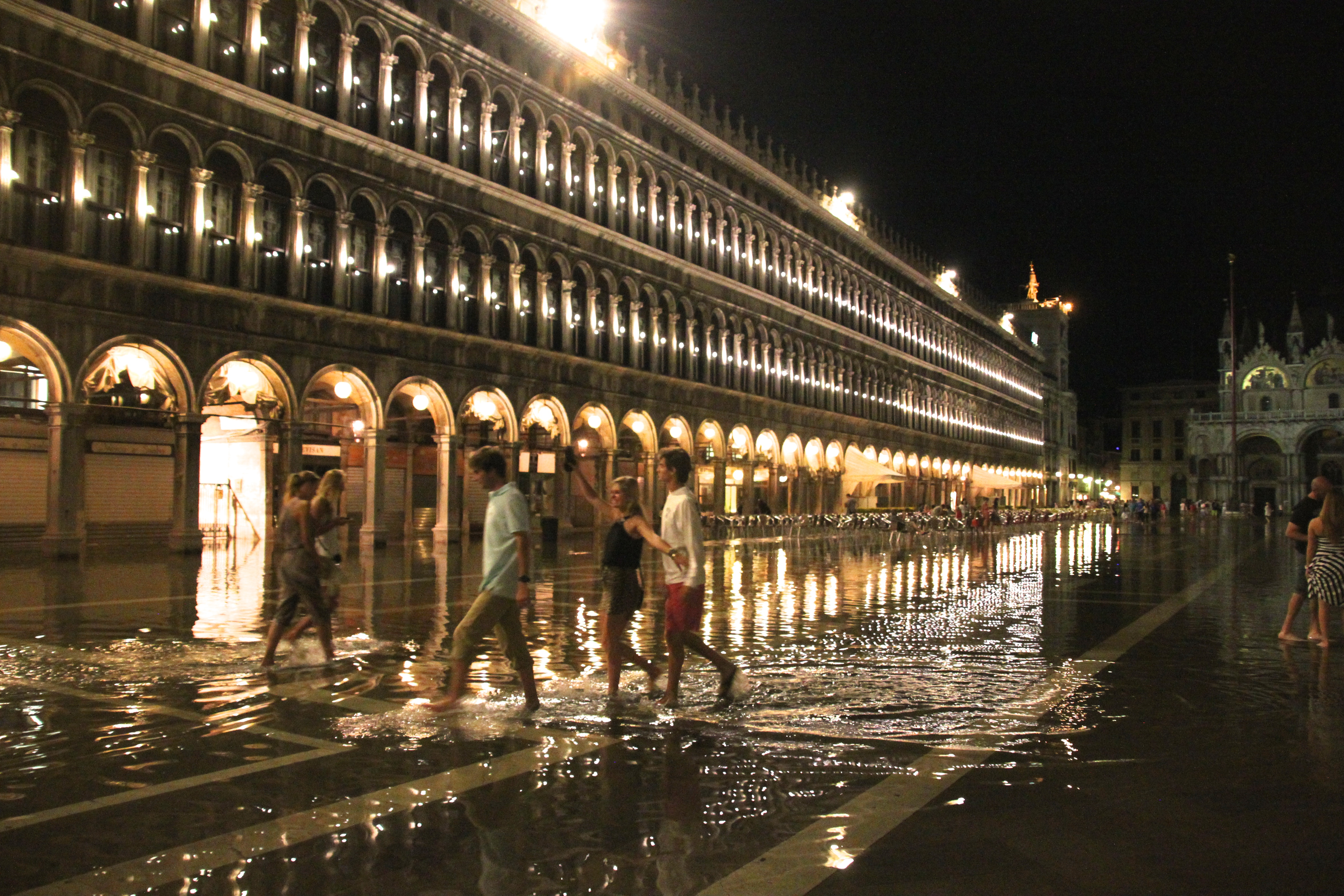 Midnight paddling in high tide waters St Mark's Square, Italy