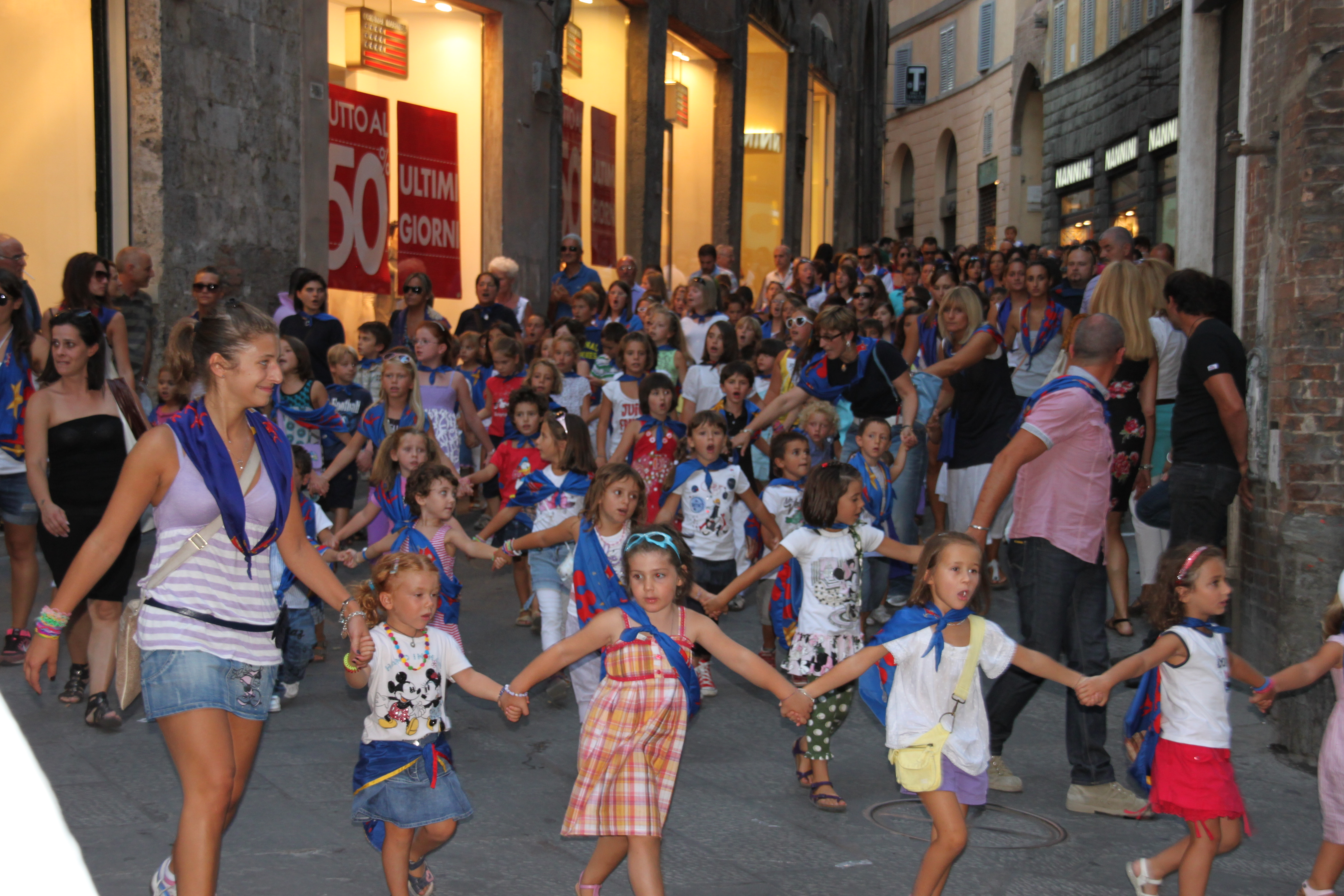 The next generation of contradaioli members parade through the streets all wearing their contrada scarf and singing the contrada hymns