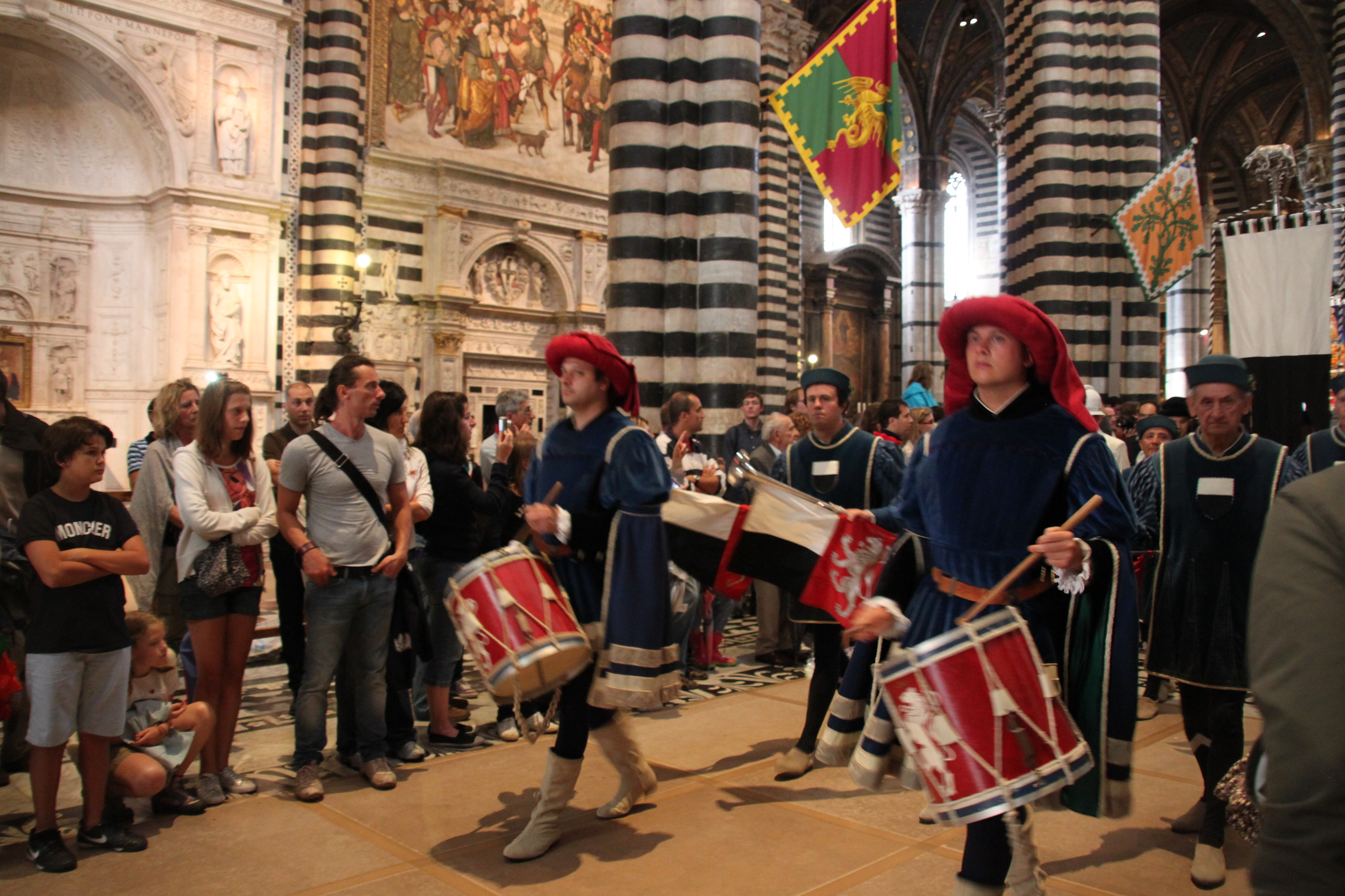 Contradas parade out of the Duomo after the blessing ceremony, their flags held aloft to the sound of drummers
