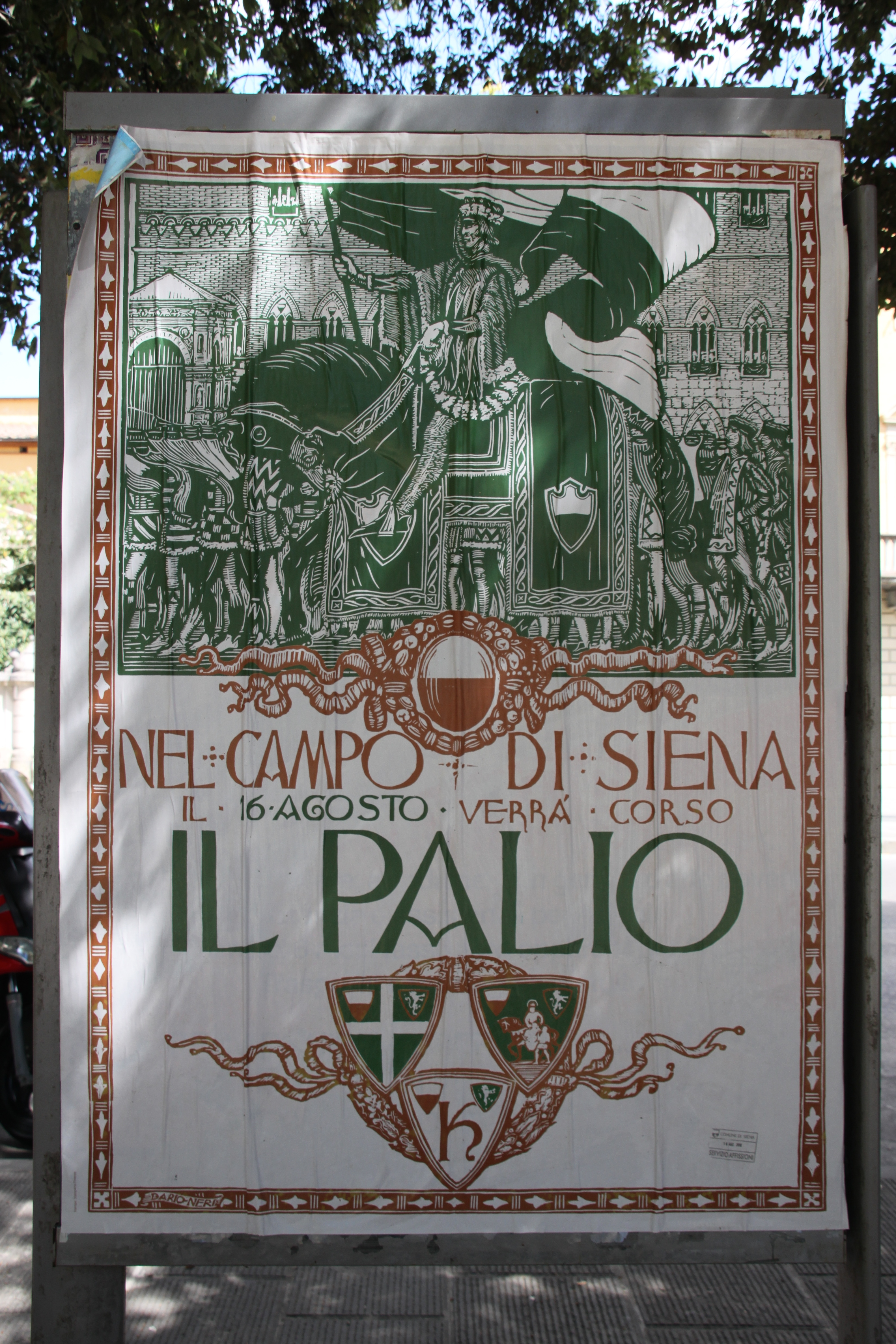The official green and red poster for the Palio di Siena in 2010 showing a man in medieval costume riding through the streets on a horse and carrying the large black and white flag of Siena