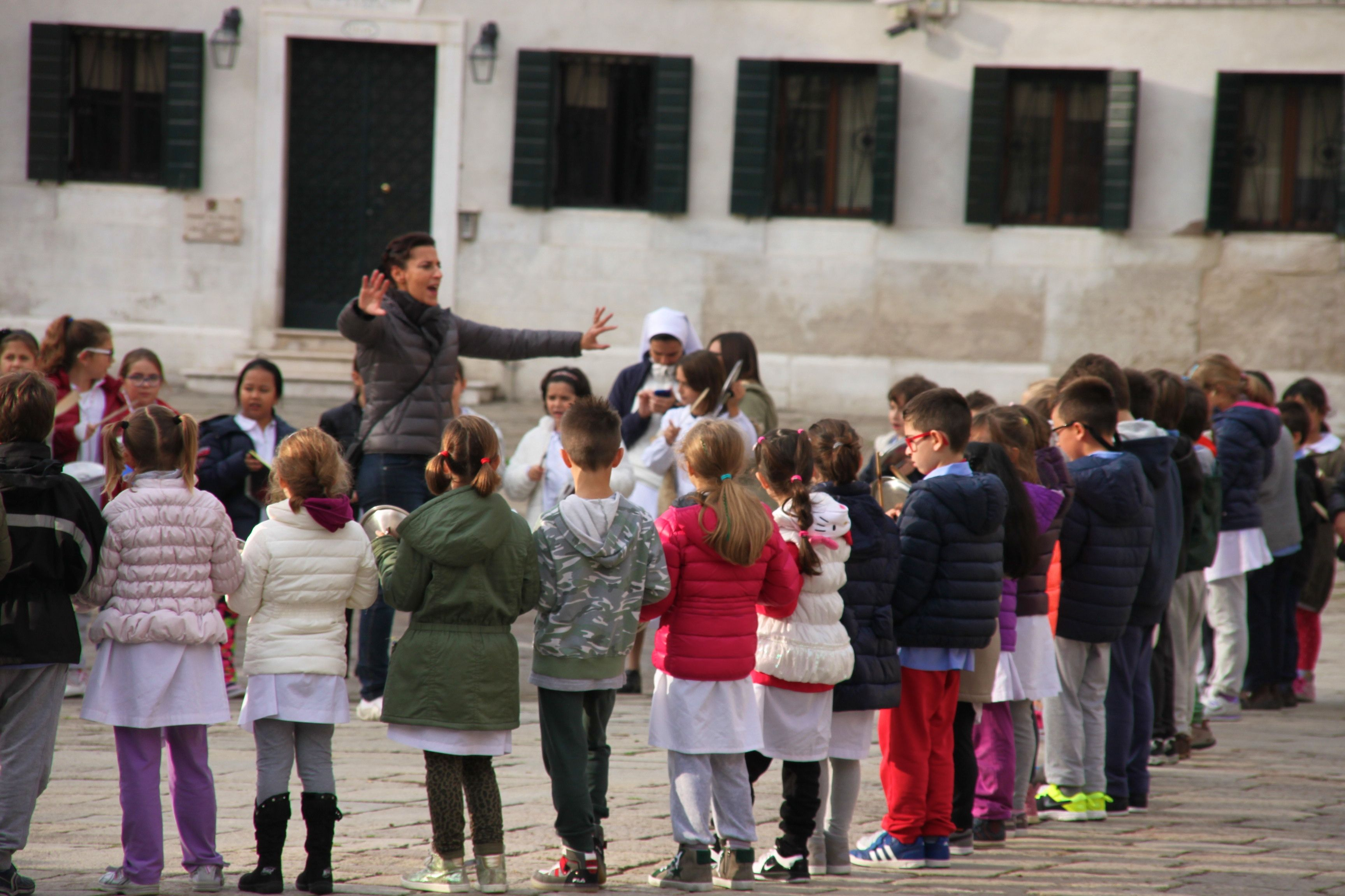 School children practice their singing and drumming in Campo San Polo, Venice