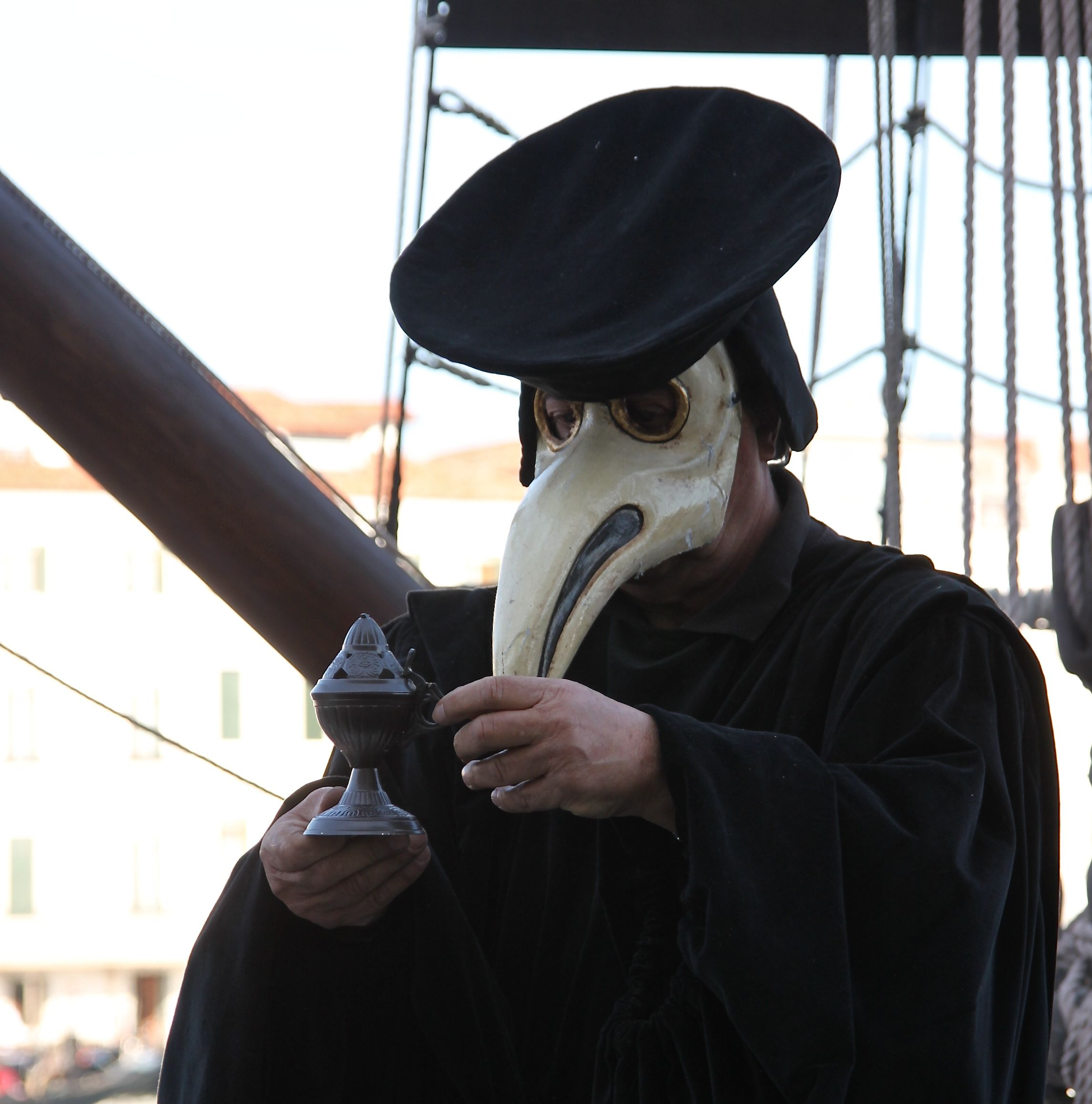 The plague doctor fumigates patients with the smoke from burning herbs