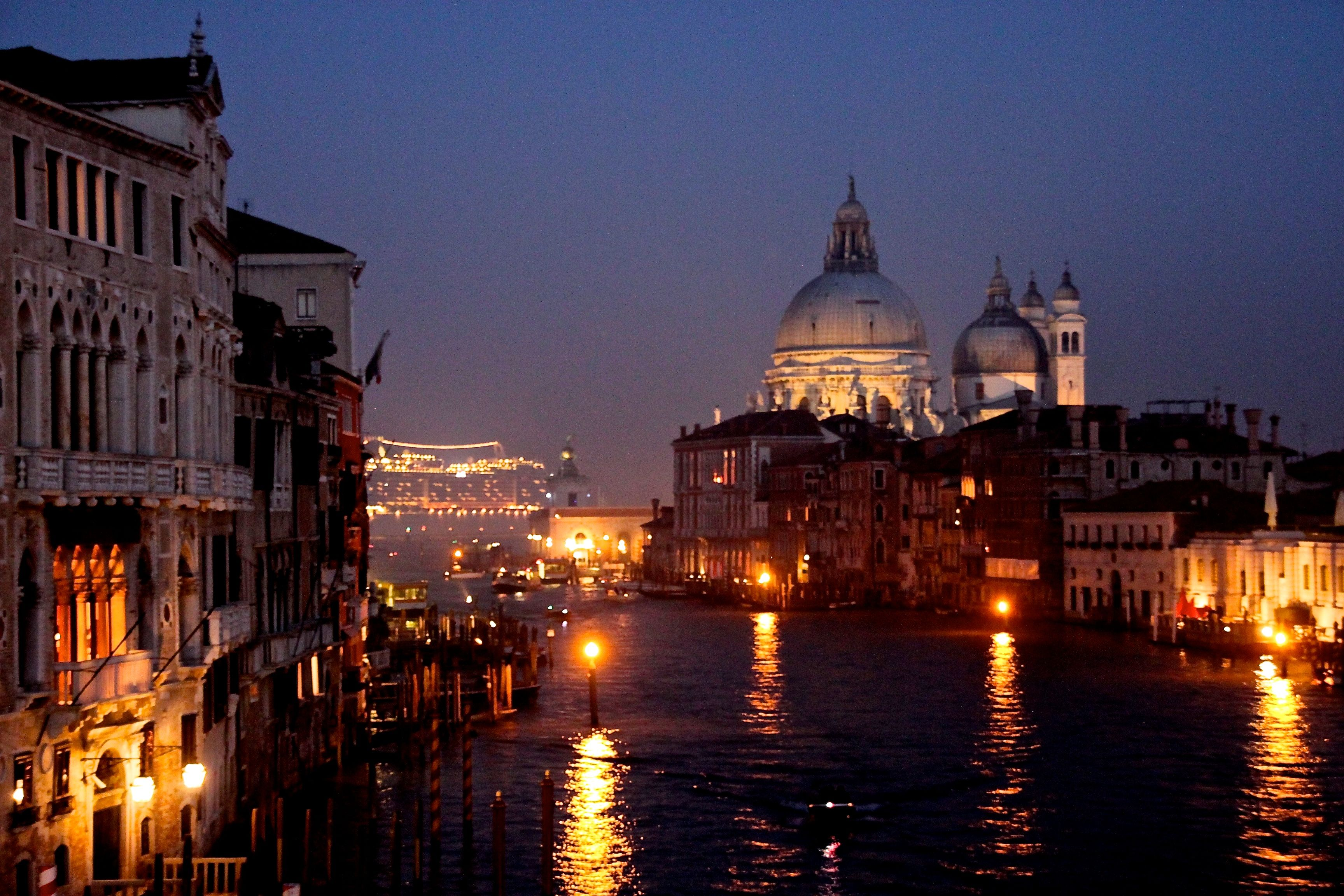 Nightime view down the Grand Canal to the Church of the Salute, with a twinkling ruse ship in St Mark's basin in the distance