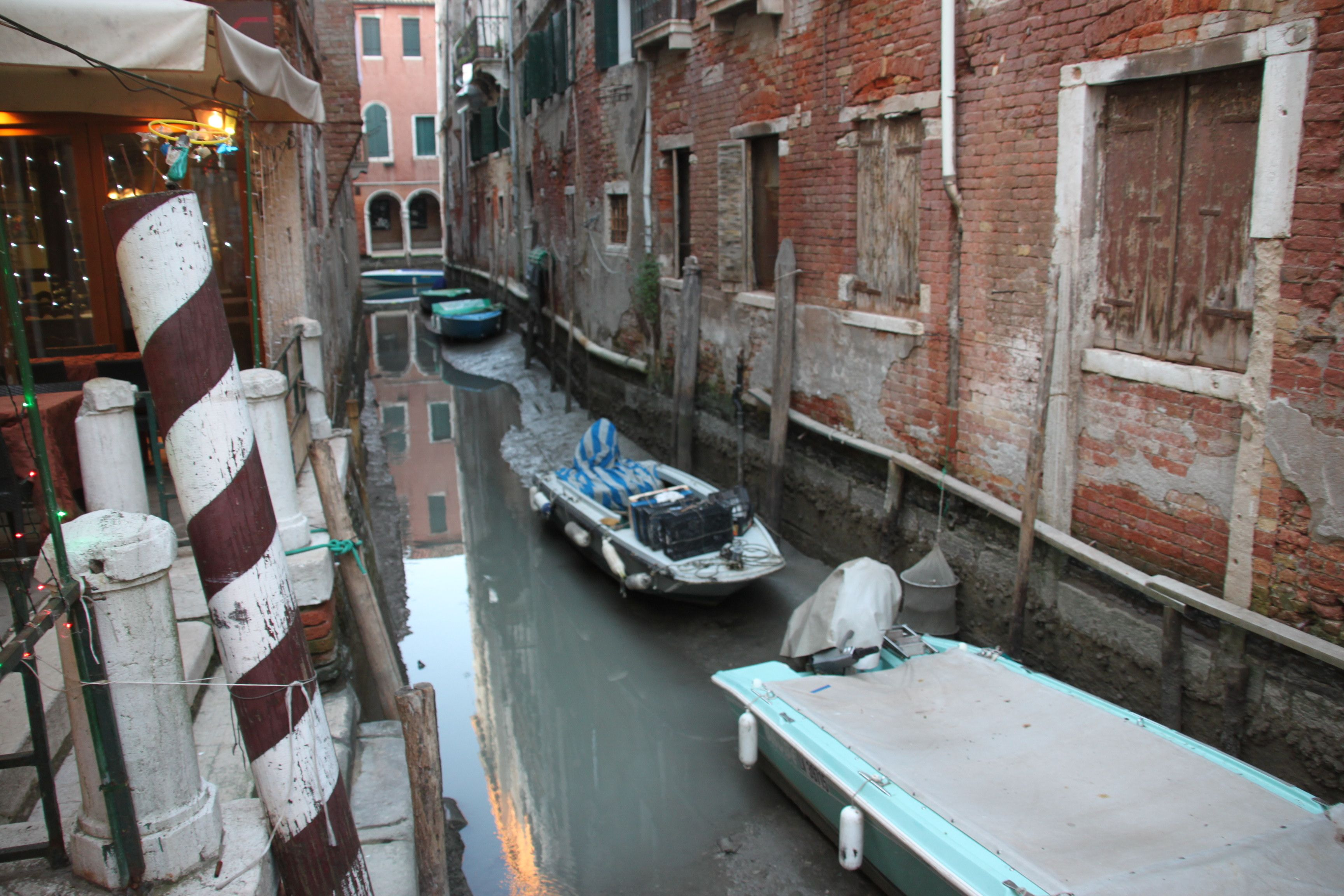 Motor boats stuck high and dry in a side canal