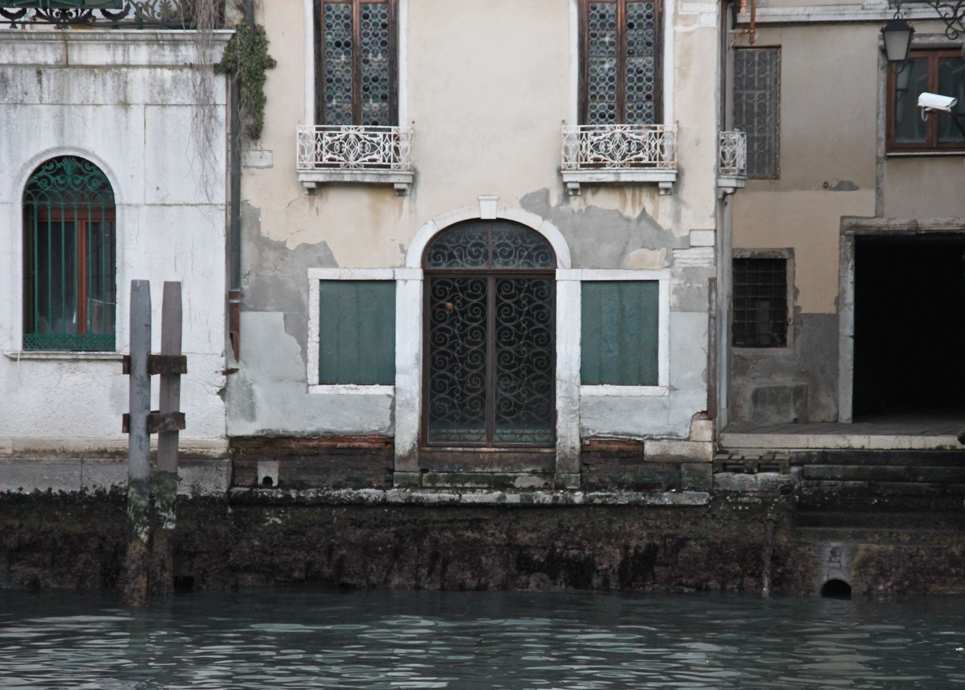 The barnacled foundations of a Grand Canal palazzo are exposed to the air
