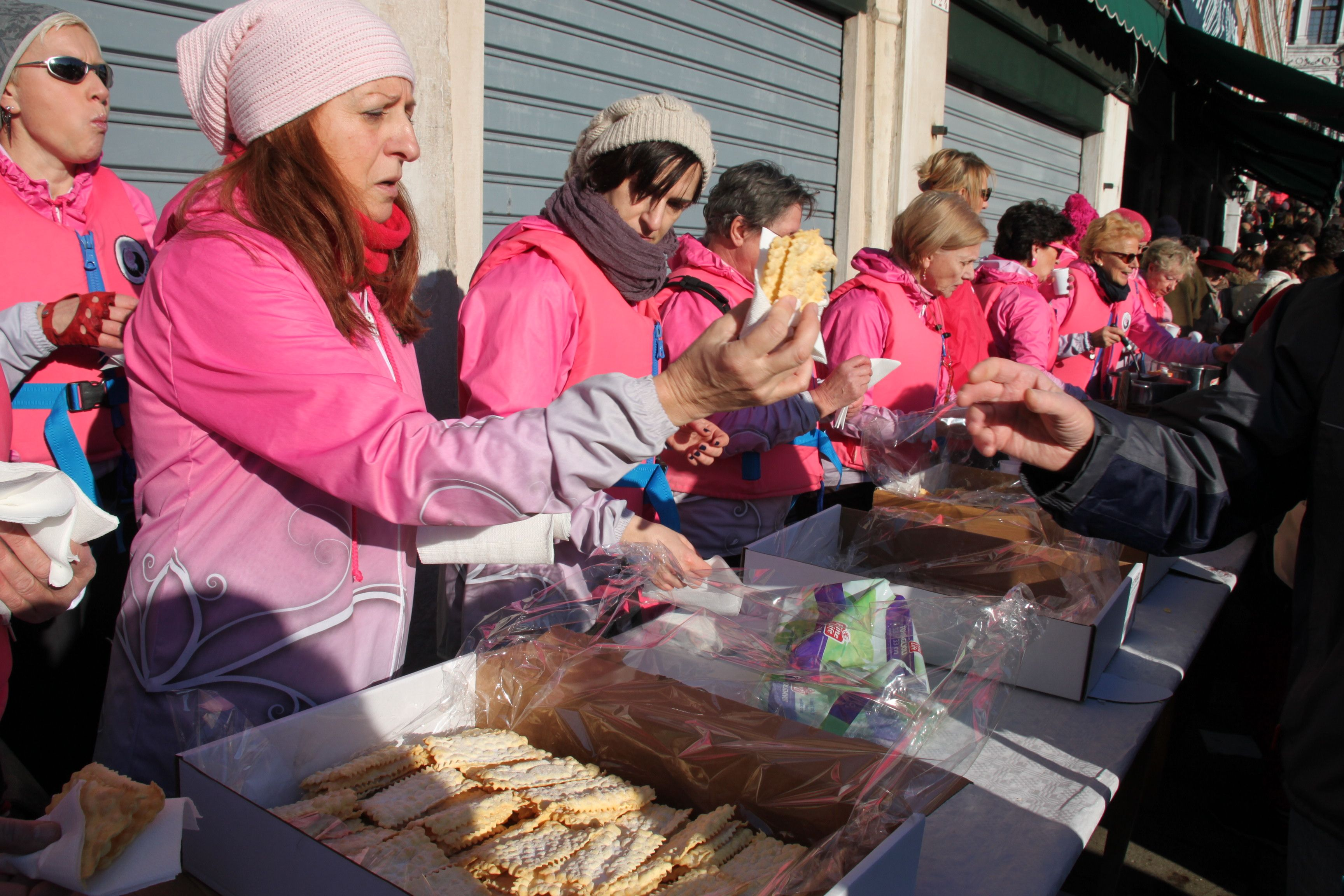 Venice's Pink Ladies dragon boat rowers hand out sugared biscuits