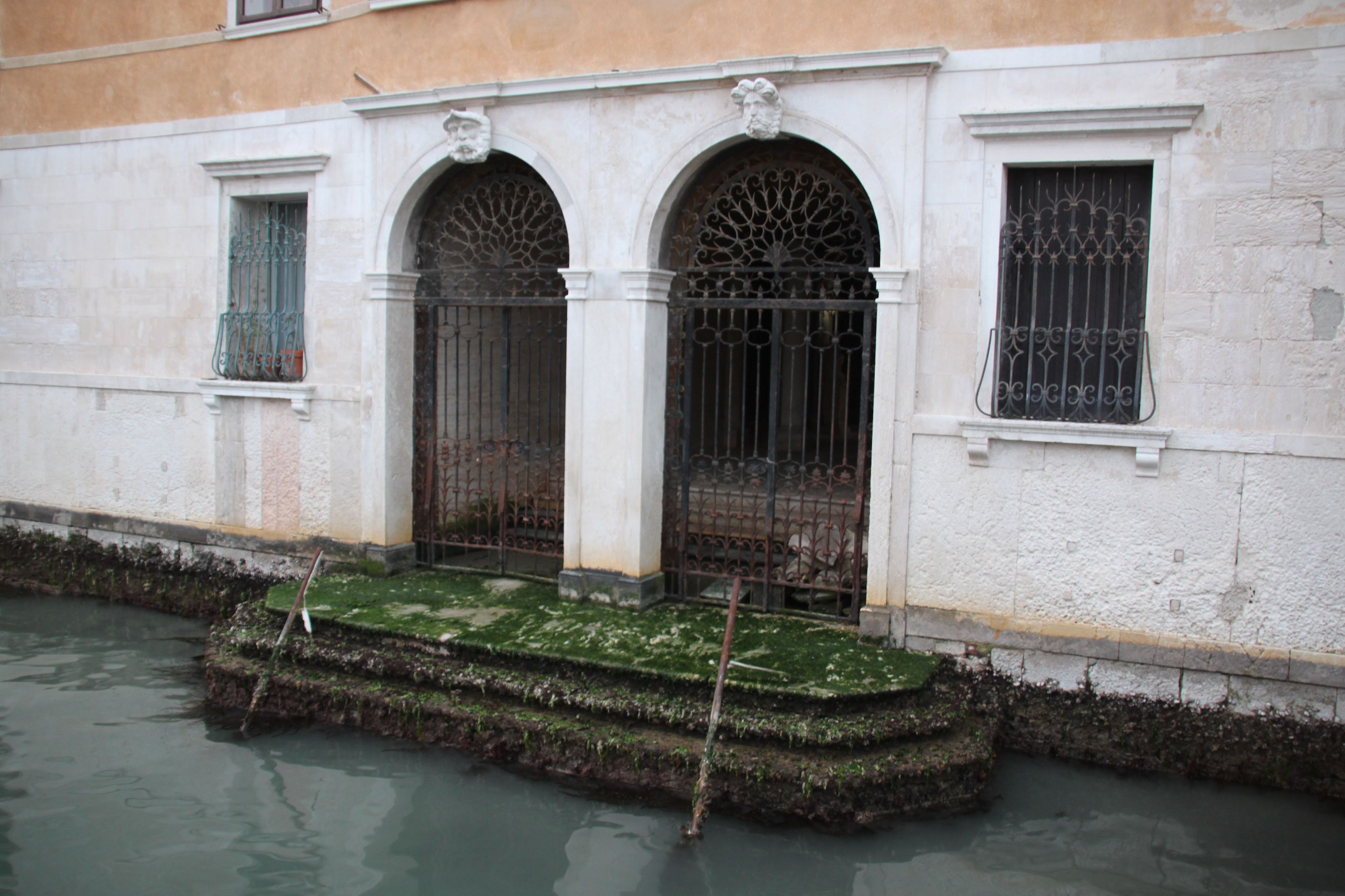 Low tide exposes the weed covered canal entrance steps to a palazzo