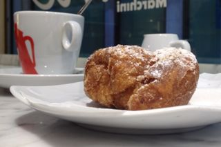 A cream-filled frittella dusted with icing sugar and ready to eat!