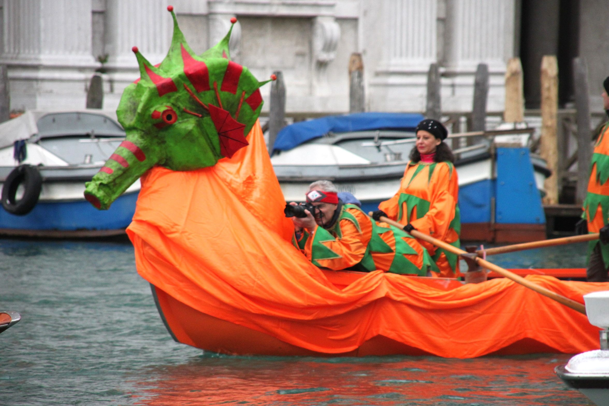 Venice Carnival Water Parade - a photographer grabs a lift on a boat decorated as a dragon