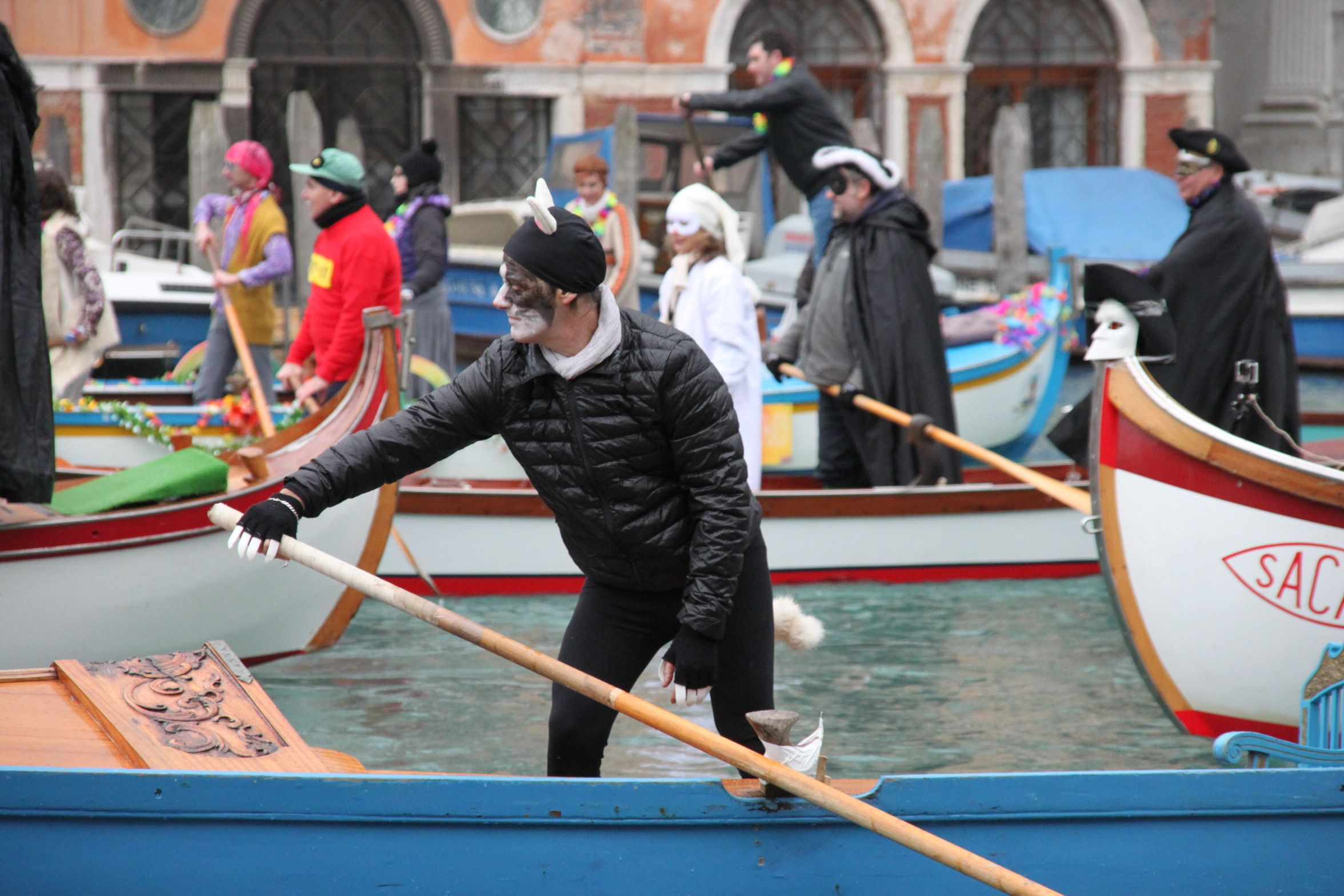 Venice Carnival Water Parade - a man dressed as the devil rowing along the Grand Canal
