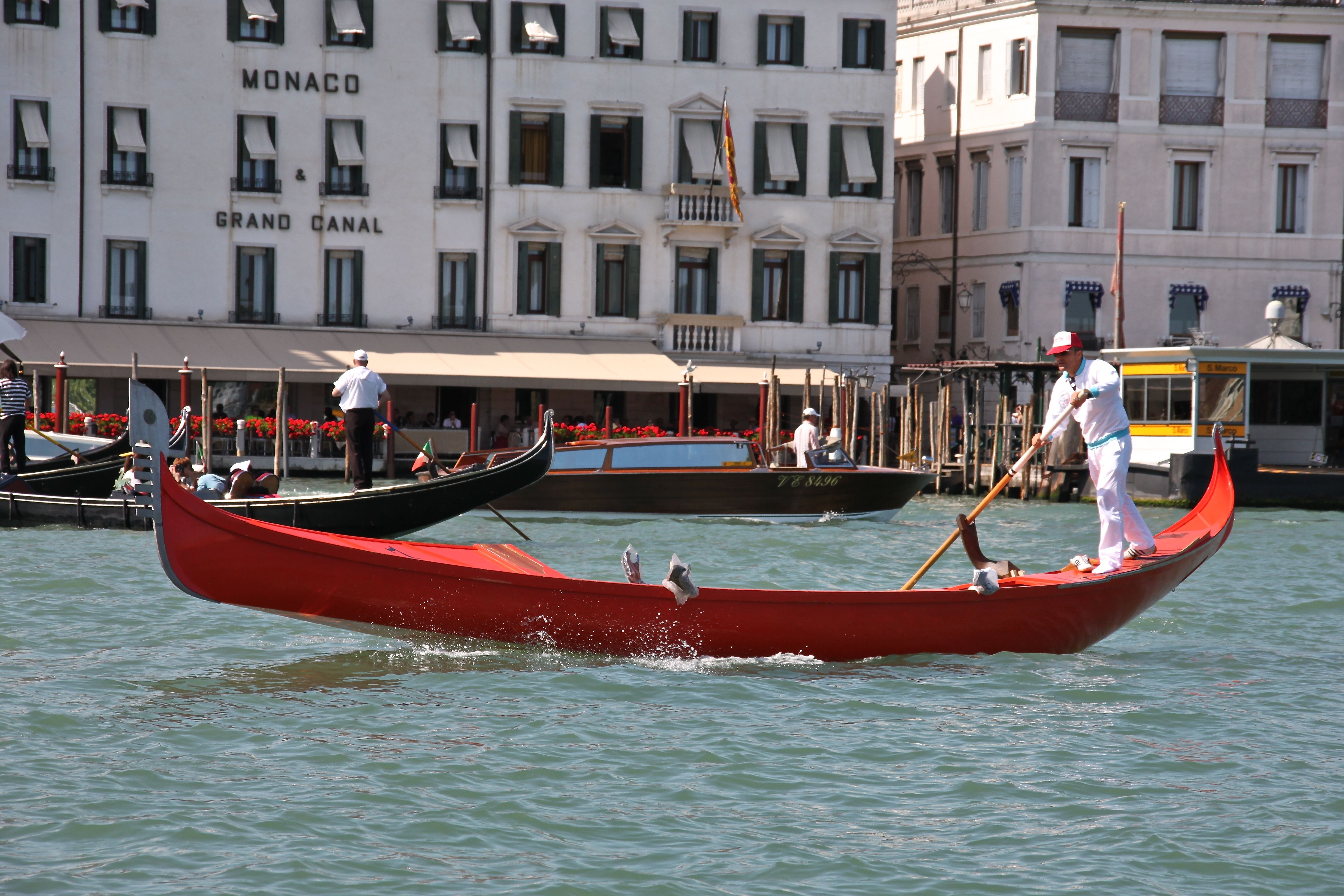 A racing gondola powers down the Grand Canal