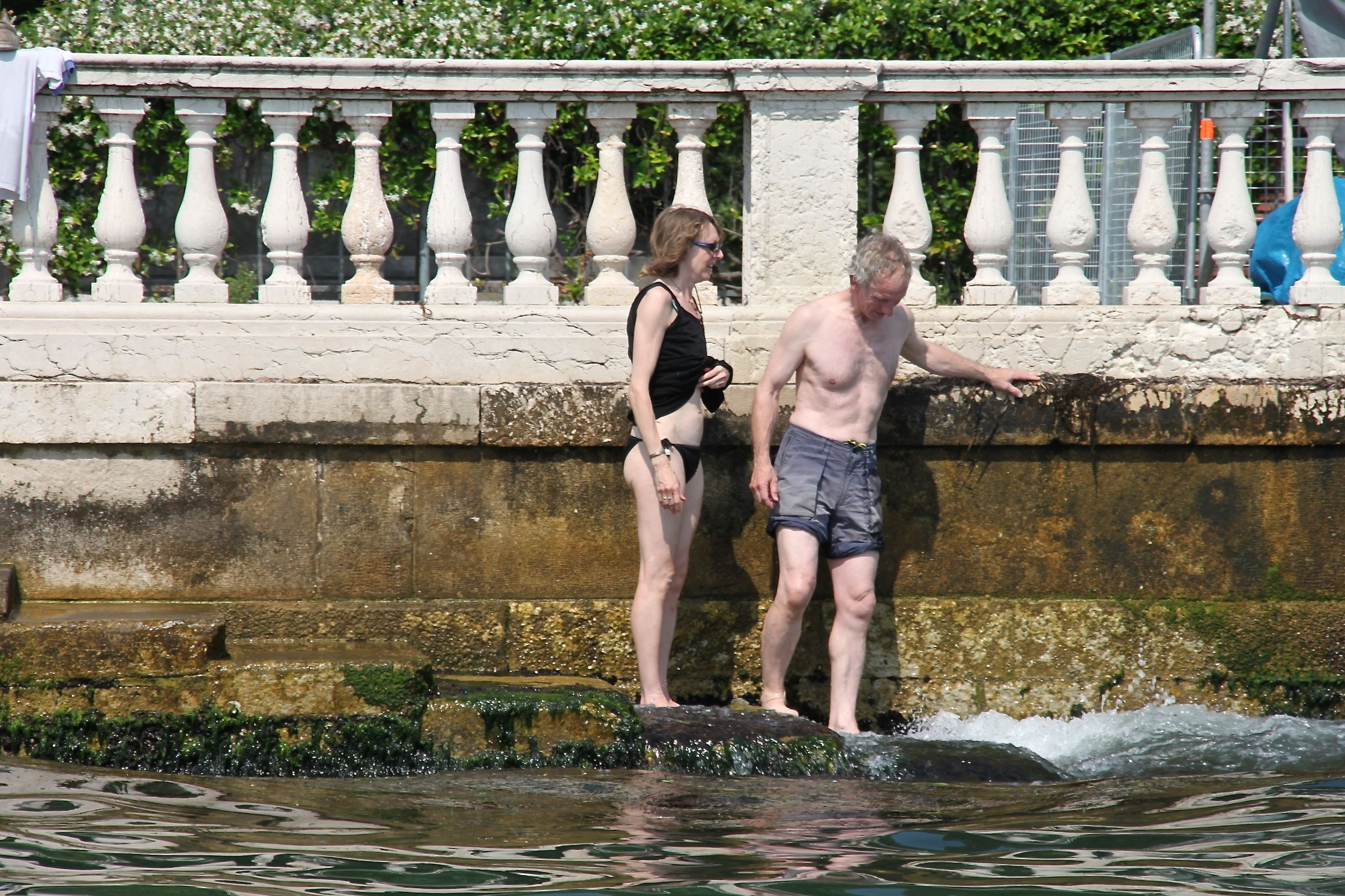 Photo of 2 tourists in bathing suits going for a dip in St Mark's Basin, Venice