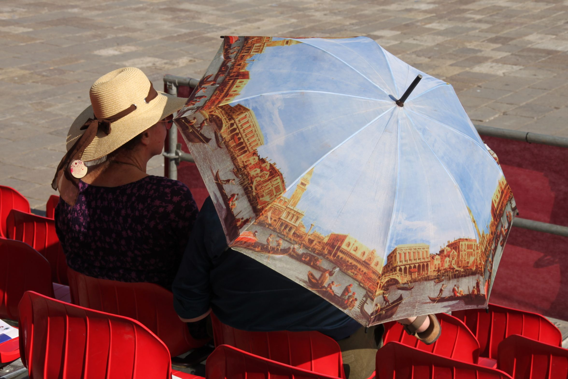 Photo of a couple sheltering from the afternoon sun under a sun-hat and umbrella