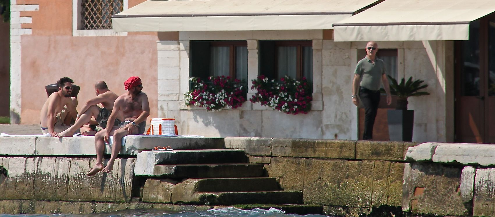 Photo of 3 topless lads sunbathing on the waterfront in Venice, Italy