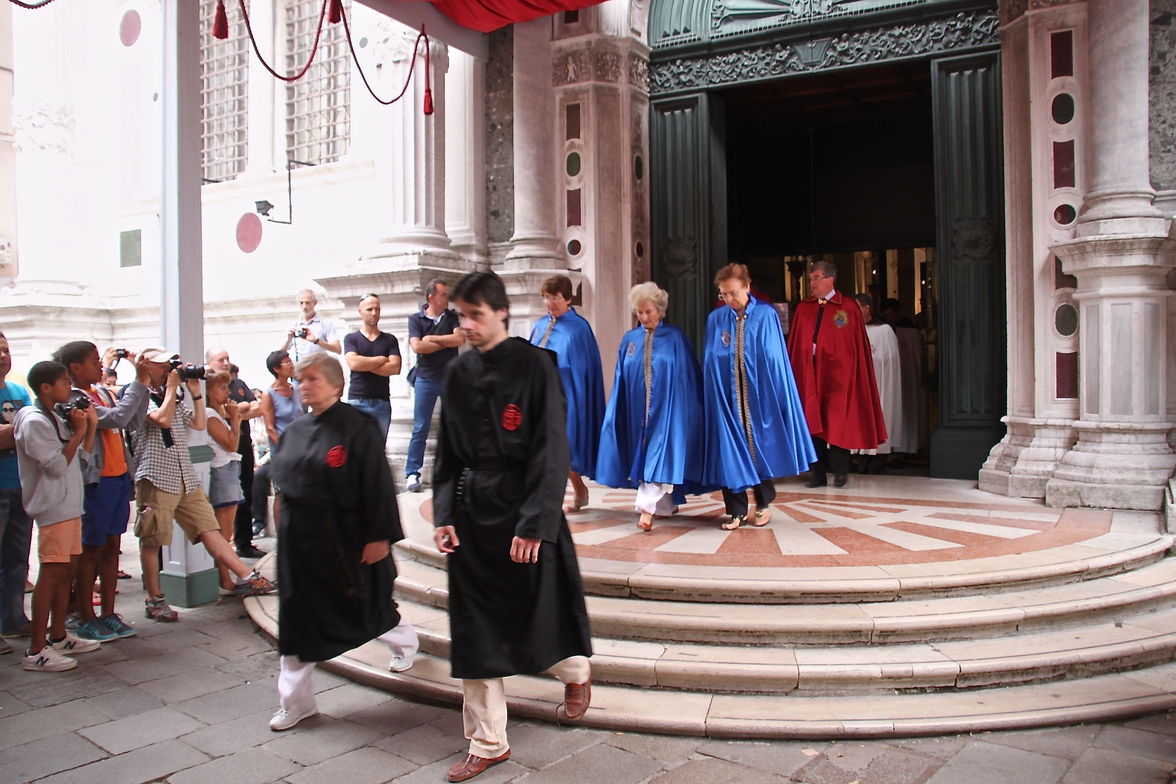 Robed members of the confraternity of San Rocco process from the scuola to the church for mass