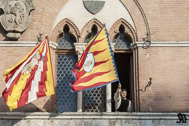 Seven contradas are automatically entered to race as they missed out last year and then 3 more are chosen by lot and their flags are flown from the Palazzo Comunale town hall - seen here are Valdimonte and Chiocciola
