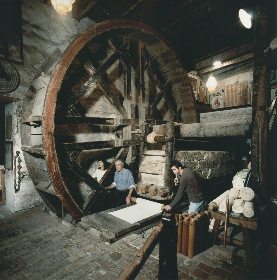 Man power turns the enormous mangano wheel to move the stone slab and press the cotton (Photo courtesy of the Antica Stamperia Artigiana Marchi)