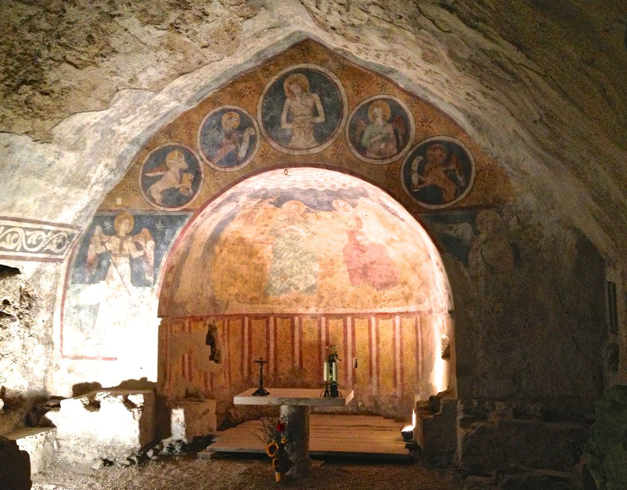 Brightly coloured frescos emerge from out of the darkness in the mysterious underground chapel in Narni, Umbria