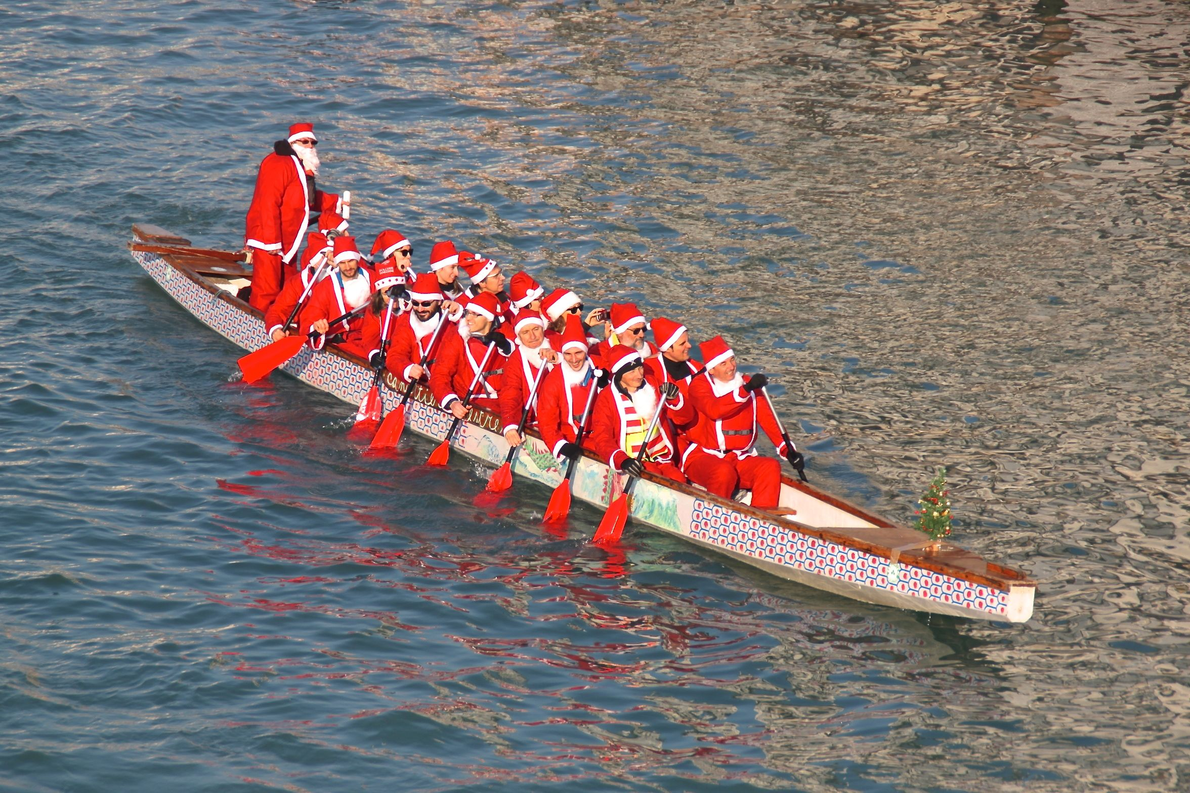 A dragon boat-load of babbo natale rowers on Venice's Grand Canal